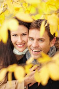 Lachendes glückliches Paar hat Spaß im Park im Herbst